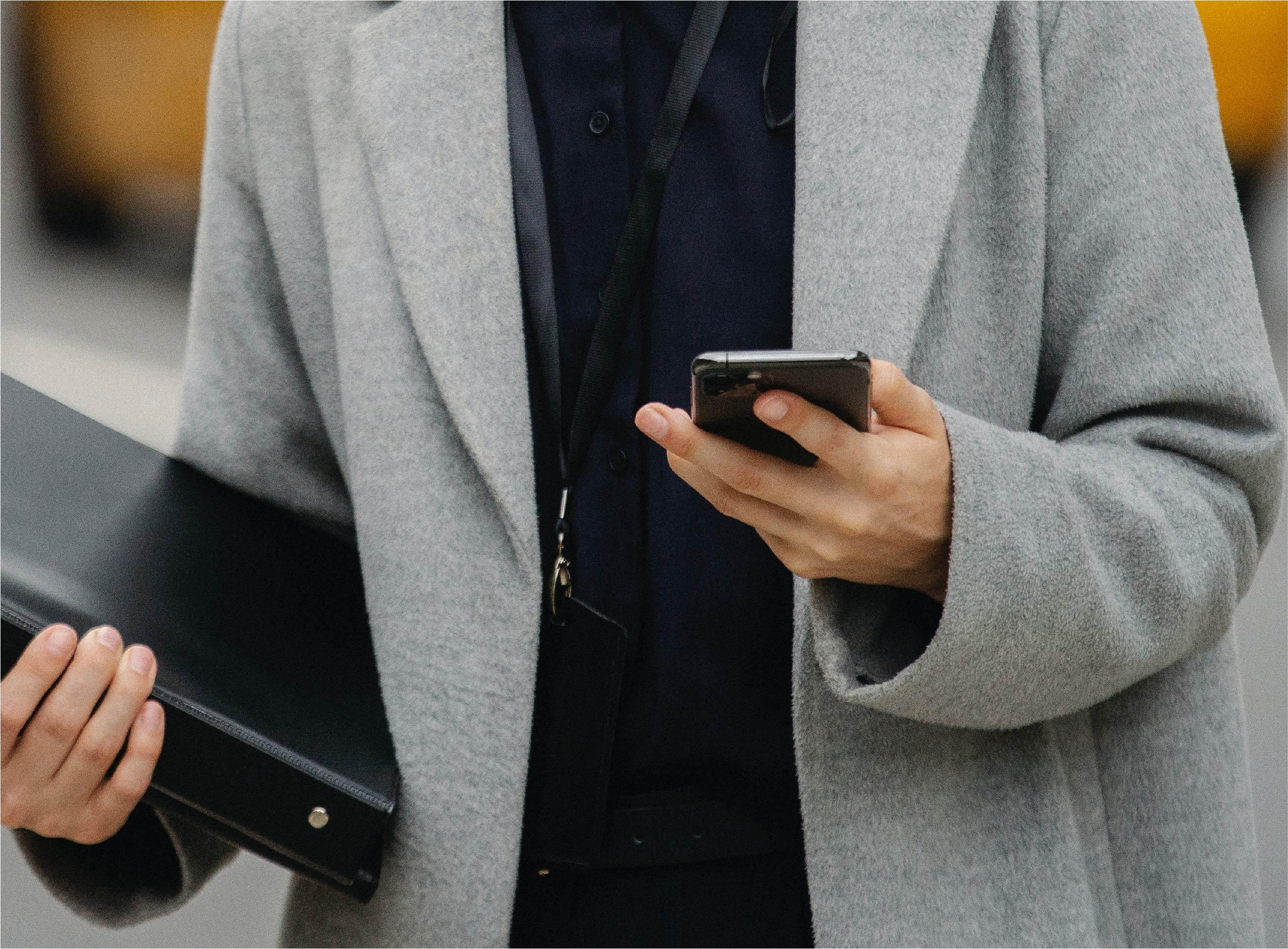 Personne sur son portable avec un dossier à la main