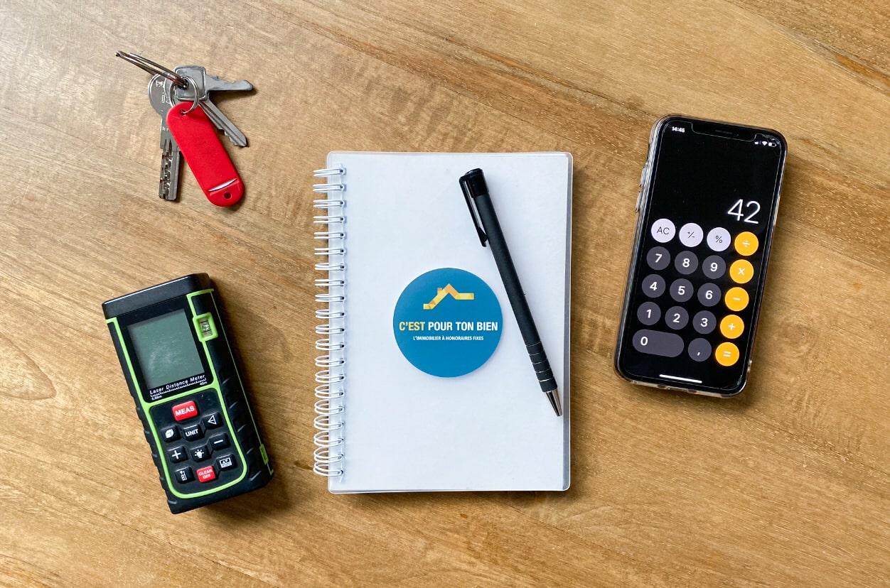 Estimation immobilière avec télémètre, carnet et calculatrice